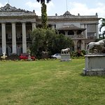 some marble statues in the garden around the building