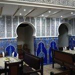 Parte del restaurante Al Kasbah con fachada a una alegre, concurrida calle salpicada de tiendas