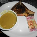 Grilled ham and cheese sandwich with split pea soup.
