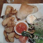 Chicken, brie and cranberry filo pastry parcel with wedges, salad, sweet chilli sauce and sour c