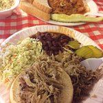 pulled pork sandwich with red beans & rice, cole shaw and jambalaya in the back