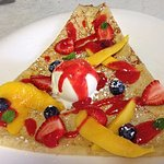 A crêpe with fresh mango, strawberries and blueberries, vanilla ice cream and a raspberry coulis