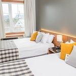 Chambre à coucher comprenant 2 lits queen, téléviseur, air climatisée et Wi-Fi.