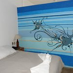 One of 2 beds in room; cute wall mural