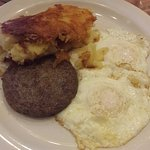 Over easy eggs with potatoes and sausage patty