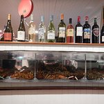 Live lobsters in the tank and display of wines available