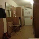 Entrée de la chambre avec rangements, mini bar et TV