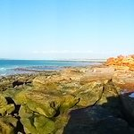 Panoramic of Gantheaume Point including lighthouse, bath, and varied colours of the coastline.
