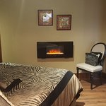 Gabriel's Suite bedroom with armoire closet and electric fireplace.