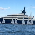 Steven Spelberg's mega-yacht hanging out with jr sailboaters...