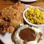 Fried chicken breast and leg with mashed potatoes and corn.