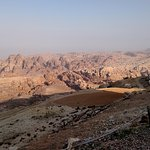 Petra is hidden within the rounded sandstone mountains in the center.