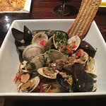 Clams and mussels with pico and cilantro on top of noodles with white wine sauce
