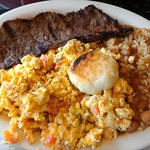 steak breakfast with eggs, beans and rice and corn cake