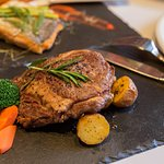 Angus Rib Eye Lib on served with roasted potatoes and sauteed vegetables
