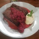 Yummy chocolate brownie with berry coulis.