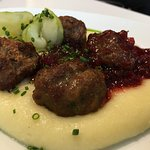 Swedish Meatballs served on top of creamy mashed potatoes with pickles, lingonberries, and chive