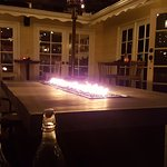 Fire table surrounded by a sofa on the outside patio