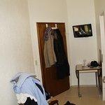 Geöffnete Badtür, Fernseher an der Wand, Tür schräg und ein kleiner Tisch
