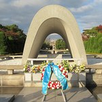 A wreath in front of the Cenotaph for the A-bomb Victims with the A-Bomb Dome in the background.