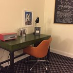 Desk in corner of room with retro radio, chair, and chalkboard