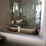 Hubby in the bath! There is an electric blind for the bathroom window, for privacy