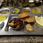 Chicken dish in the red with Dal,Sambhar,potato veggies,Sweet Dish, Rasam and Papadum and puris