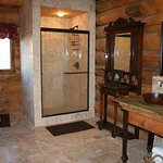 Huge master bath has travertine stone shower, clawfoot tub, and double vanity.