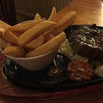 Ribeye steak, medium, with onions and a flat mushroom.