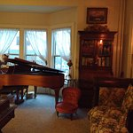 Other side of large sitting room past christmas tree. Baby Grand Piano.