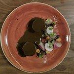 Guajolote en recado negro perfumado en cascarilla de cacao, vegetales fermentados y cebollas con