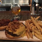 Burger with crispy shallots and bacon, accompanied by garlic parmesan fries and a double IPA