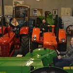 Part of Deering tractor collection with guests enjoying a ride.