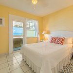 Bedroom of unit 1 with view of the sea and access to the private veranda and beach beyond.