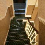 Looking down to bathroom doorway (2 bathrooms). Note angle turn on steps.