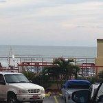Looking between buildings at parking area, pool and ocean.