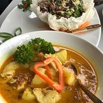 Yum yellow curry with delicious chicken larb in background