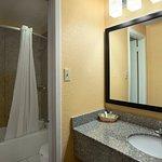 Bath tub with granite tub surround and granite modern vanity.