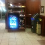Front Lobby fridge filled with drinks, shelves have snacks and toiletries and cash machine