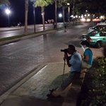 Sitting on the street(Malecon) in front of the hotel with cameras ready.