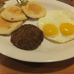Breakfast of pancakes sausage patty and eggs