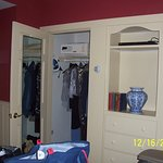 Photo of closet, ironing board,iron, safe, mirror and plenty or hangers.