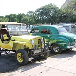 Vintage cars parked, including Jeep Willys