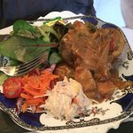 Chicken curry on baked potato, with salad leave, coleslae & carrot