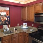 Clean compact kitchen with fridge, microwave and full stove. Plus kitchen utensils
