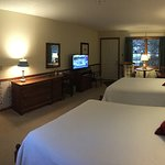Deluxe room with two queens, dressing room, sitting area, and refrigerator.