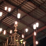 The open-air upper level has a high tin roof and jar/bottles as lights.