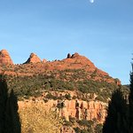 The moon rising over the red rocks.