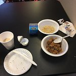 Spartan breakfast offering of bagels with cream cheese, cereal with milk, oatmeal, small muffins