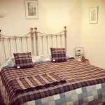 Comfortable kingsized bed with woollen blankets.